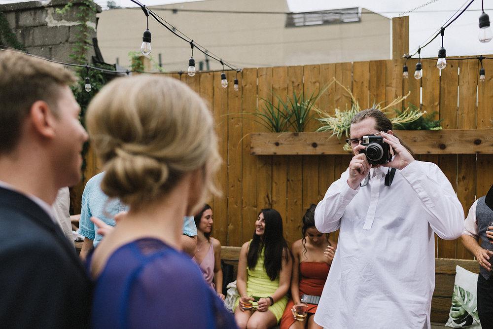 urban-downtown-toronto-wedding-fat-pasha-torontos-best-wedding-photographer-3b-photography-film-photographer-analog-photography-ceremony-on-outdoor-patio-kodak-portra-800-bride-and-groom-vows-guests-watching-light-and-shadows.jpg