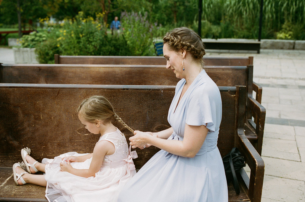 Toronto-Island-Wedding-Toronto-Best-Film-Wedding-Photographers-3b-photography-analog-photography-wards-island-clubhouse-junebug-weddings-vintage-venue-reception-getting-ready-candid-bridesmaid-doing-flower-girls-hair.jpg