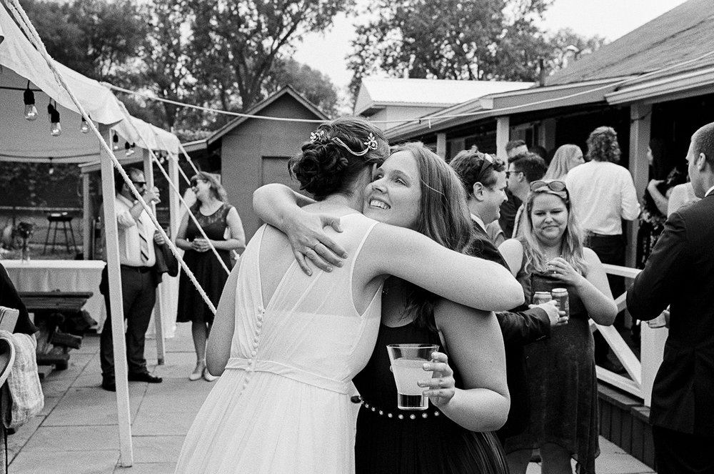 Best-Analog-Film-Wedding-Photography-Toronto-3B-Photography-Brjann-BAtista-Bettencourt-Editorial-Candid-Documentary-Wedding-photographers-Canada-Vintage-Moody-Portrait-of-bride-and-groom-candid-moment-with-bride-hugging-her-friend.jpg