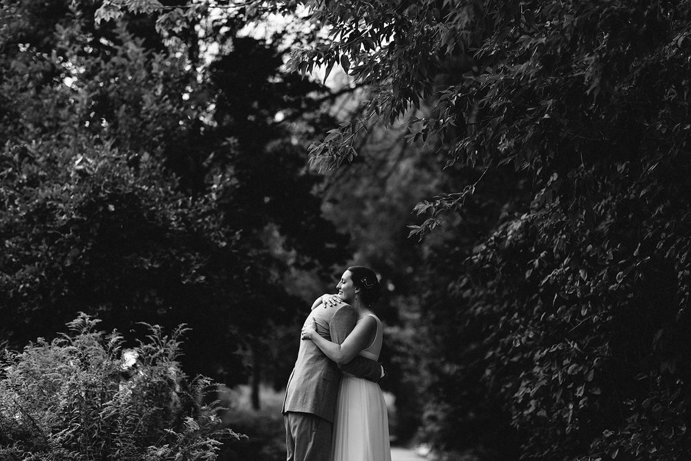 Toronto-Island-Best-Film-Wedding-Photographers-3b-photography-analog-photography-wards-island-clubhouse-green-wedding-shoes-vintage-venue-bride-and-groom-photos-intimate-candid-documentary-moments-hugging-embracing-trees-bw.jpg