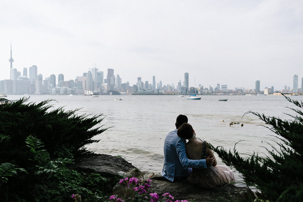 Bride-and-Groom-Sharing-Quiet-moment-looking-at-sunset-over-toronto-skyline-toronto-wedding-photographers-Toronto-island-Cafe-clubhouse-wedding-boho-hip-cool-bride-and-groom.jpg