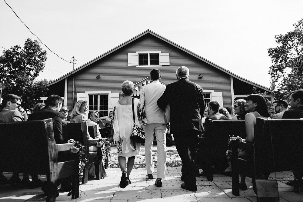 Toronto-Island-Cafe-Club-house-wedding-ceremony-photography-best-photojournalistic-documentary-wedding-photographers-toronto-hip-boh-cool-bride-and-groom-emotional-intimate-toronto-island-wedding-groom-walking-parents-bw.jpg
