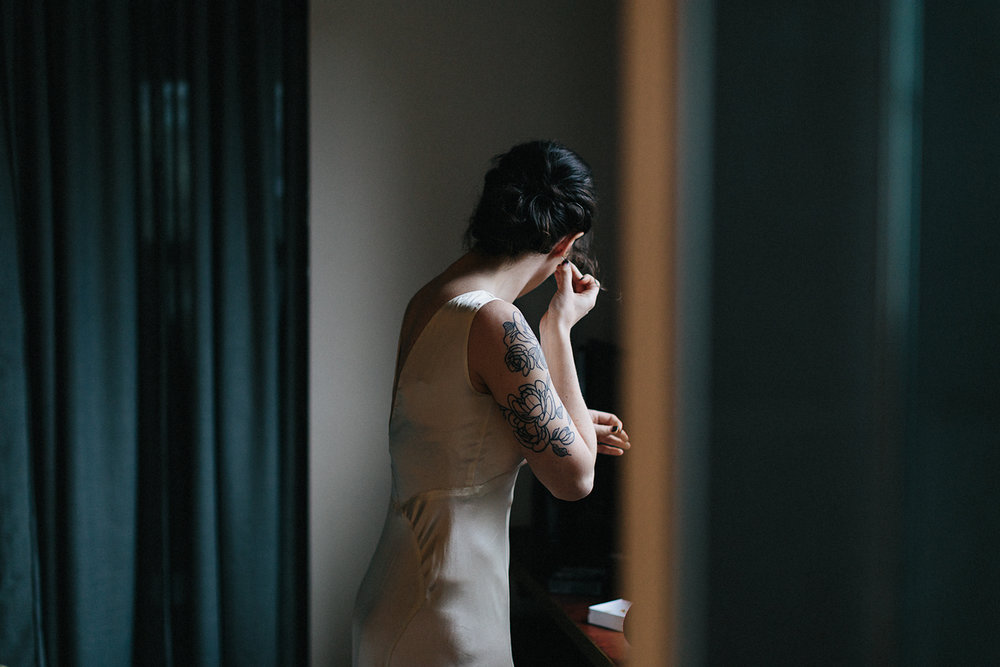 film-vintage-wedding-dress-details-silk-tattooed-bride-putting-on-earrings-Toronto-Elopement-at-the-Drake-Hotel-Torontos-Best-elopement-photographers-candid-documentary.jpg