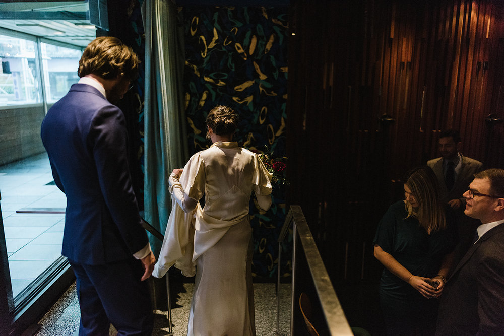bride-and-groom-entering-together-artistic-entrance-ceremony-space-moody-candlelit-cinematic-marriage-Toronto-Elopement-at-the-Drake-Hotel-pop-up-Torontos-Best-wedding-photographers-candid-documentary-photojournalistic.jpg