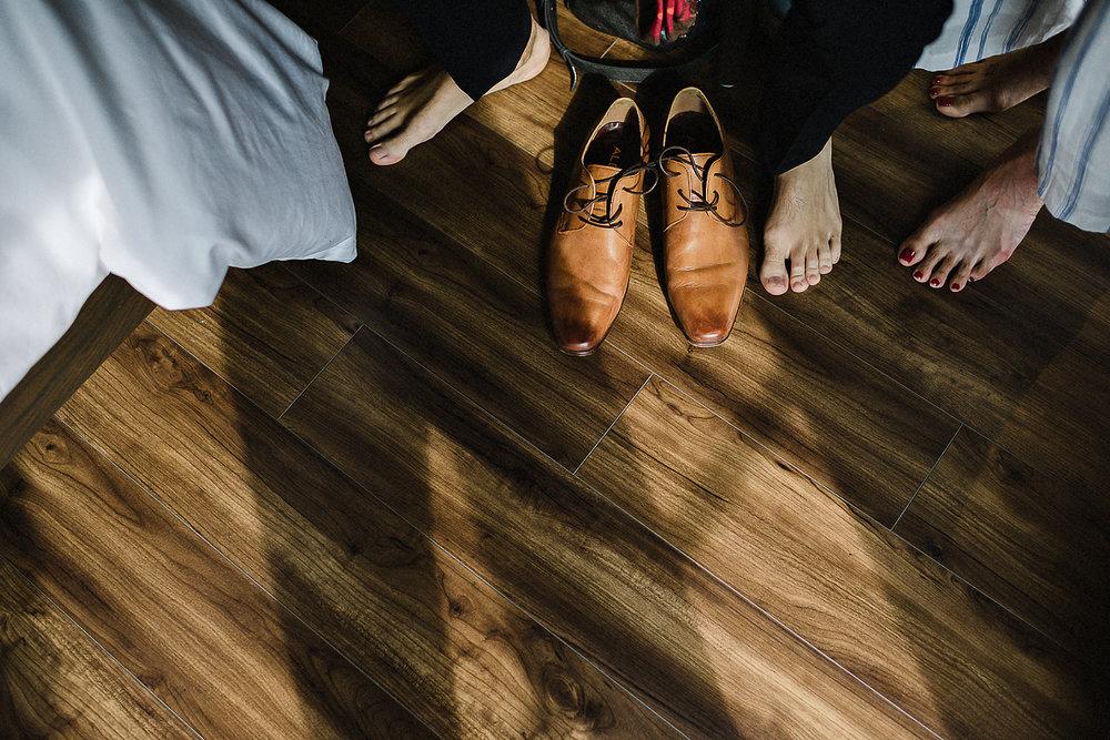 19-514-Toronto-Wedding-at-the-Broadview-Hotel-Vintage-Bride-and-Groom-Wedding-Details-Old-School-Telephone-Best-Wedding-Photographers-Toronto-Junebug-Weddings-Candid-Genuine-Moments-Groom-getting-ready-putting-on-shoes.jpg