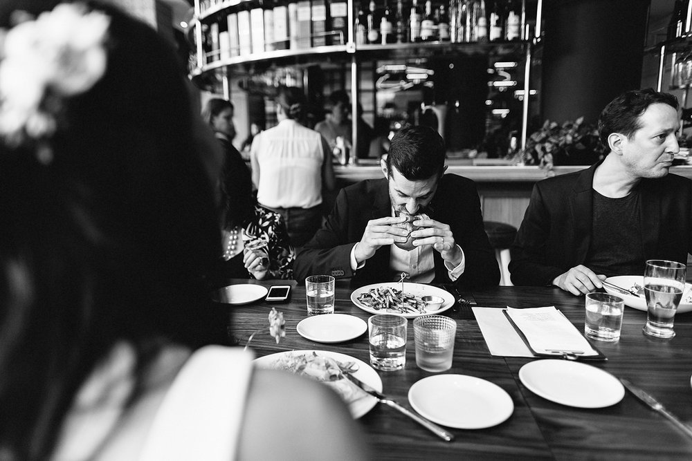 68-397-Toronto-Wedding-Venues-Broadview-Hotel-Urban-Boho-Bride-and-Groom-Best-Wedding-Photographers-GTA-Ontario-Candid-Groom-Funny--Eating-Burger.jpg