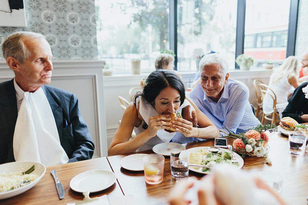 69-395-Toronto-Wedding-Venues-Broadview-Hotel-Urban-Boho-Bride-and-Groom-Best-Wedding-Photographers-GTA-Ontario-Candid-Bride-Funny--Eating-Burger.jpg