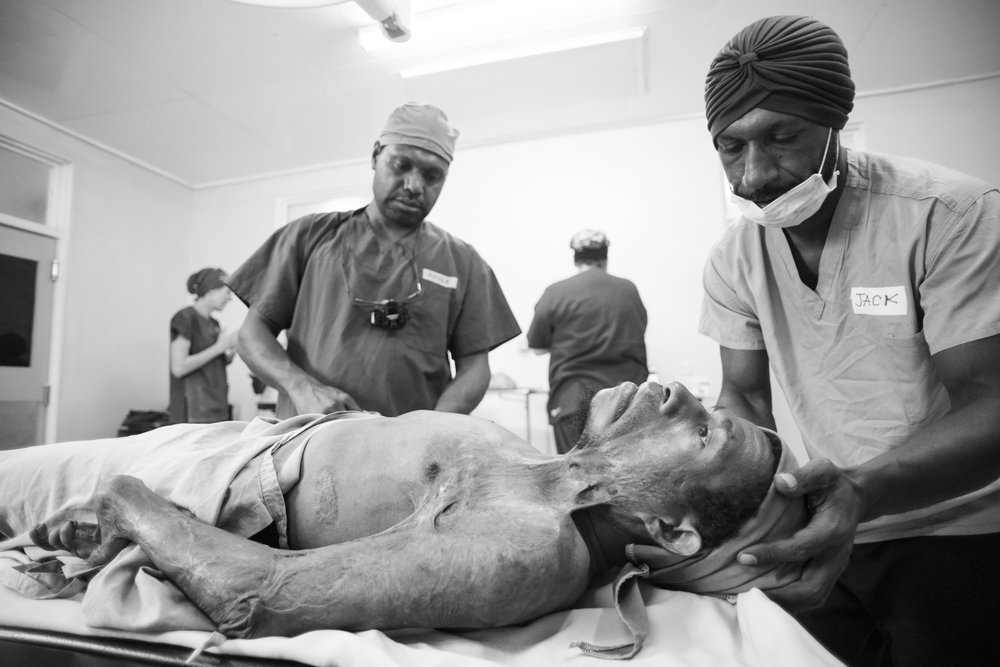 Vanimo, Papua New Guinea.  Lemeck lays quietly on the operating table, awaiting Nkule the local Plastic Surgery trainee and Jack Justice ( real name! ) to begin anaesthesia. The full extent of his burns is visable, and upon touching his cold scar tissue I further understood his lack of mobilty as the skin felt like leather.