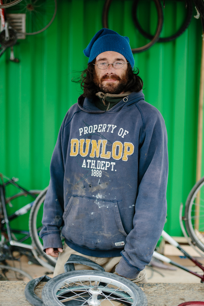 "Eoin, 36, Dublin Had just arrived to continue running the bike repair shack in Dunkirk Camp. ""A friend of mine was here a month ago just before the police went into Calais.  It was because of her, she saw on the list of things needed that there was bicycle stuff and bicycles are my passion and I'm unemployed at the moment at home so she was like 'come on'. [I came] just to lend a hand really.  I'm unemployed and when you are on the dole they give you two weeks paid holiday so I put in my application for that and set off. I'd be working as a bike mechanic.  Most of last year I was trying to set up my own bike shop in Dublin but as the economy is getting better rent was going up and up in the capital so I was priced out of the market just as I was about to get going. I'm going back to college in September to study engineering. First of all this camp i was amazed to see how well structured it was.  I'd heard stories of the jungle - tents in muddy fields.  So I was expecting a lot worse than the infrastructure here.  I was expecting it to be akin to a music festival - very temporary structures - massive big tents and that's it.  I was surprised to see so many solid structures on site. I've been following what's been going on and my mother works as a psychologist with refugees and asylum seekers in Dublin.  She has brought home some horrific stories of what her clients have been through and that's been my knowledge base of what's been going on.  I'm very much looking forward to getting chatting to more of the residents. I think this is an emergency situation.  The people who are in the most dire need of home.  There are structures in place at home to take care of people.  Anything any european citizen can do to help is greatly appreciated and much needed. I think a lot of the political reactions from countries in Europe doesn't make a whole heap of sense.  If you look at influx the long term is beneficial.  Culturally, economically, they tend to take low paid jobs that locals might not want to do and everything seems to suggest it's an overall benefit. I think of the coming decades it's going to be something that everybody is going to have to learn to deal with .  With global warming a lot of places are going to become uninhabitable in the next few decades so there is going to be mass migration from other parts of the globe.  So we need to learn to be open to helping these people as opposed to just shutting our doors and trying to ignore it""."