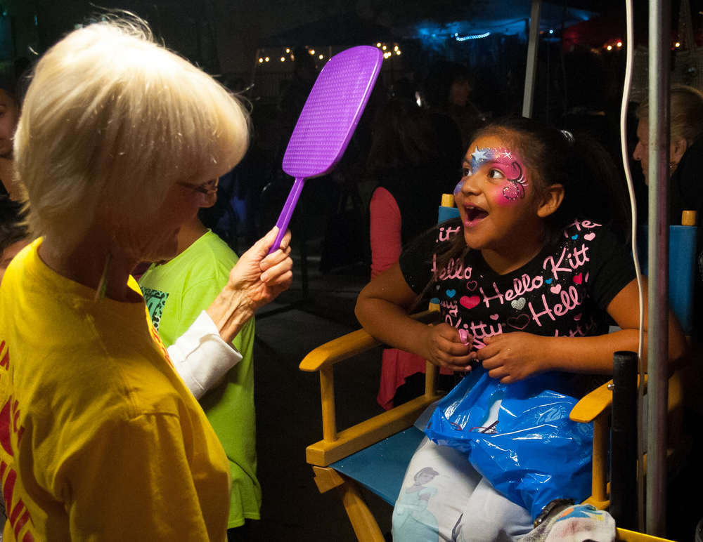 Pam Dickson holds up a mirror for 8-year-old Jaeleen Bustillos to admire her work at a face painting booth during the Wednesday night Farmer's Market.