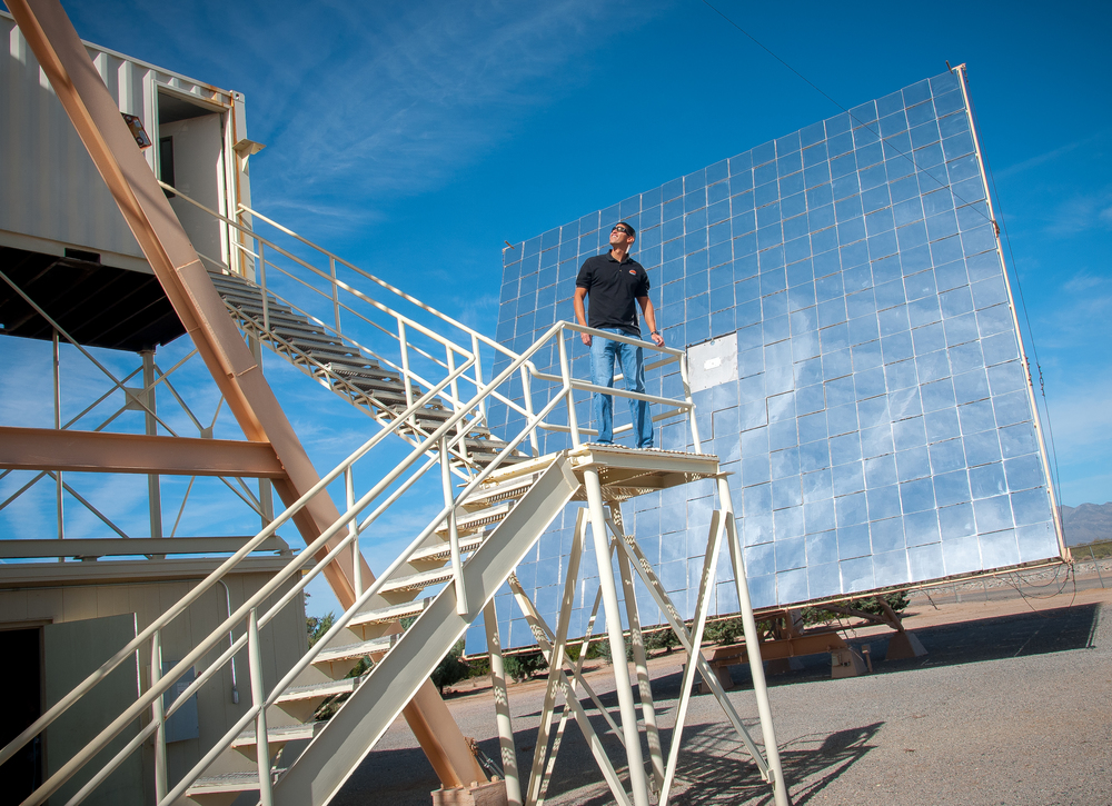 White Sands Missile Range electronics engineer Jose Enriquez stands in front a heliostat, a 40-foot wide, 36-foot high perpendicular plane of 180 2'x2' mirrors which will help focus sunlight onto a sample of the mineral williamsite serpentine as part of a space asteroid mining test at WSMR.