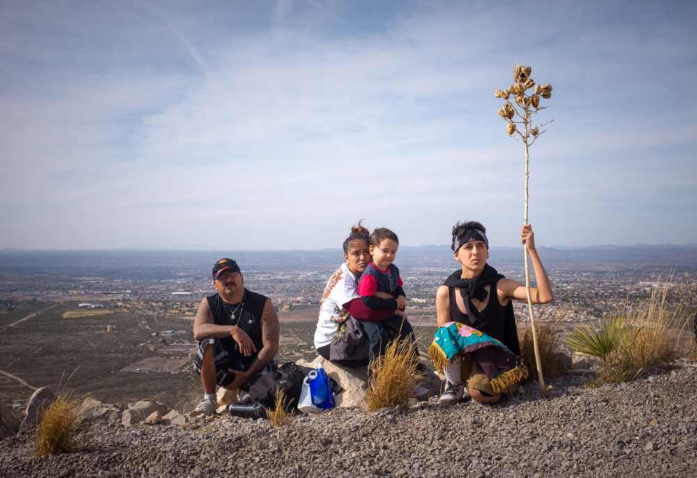 "Mike Montes, left, his daughter Celeste Montes, grandson four-year-old Niko Montes and son Jeremiah Montes listen to Bishop Oscar Cantú performing the Catholic Mass on the top of Tortugas ""A"" Mountain on Friday morning. Hundreds of people converged on the mountain as part of Tortugas Pueblo's three day Our Lady of Guadalupe Fiesta."