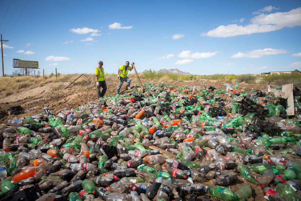 Paul Molano, left and Matthew Ford, working for Kleine Motor Company, clean up a large spill of soda bottles after a truck carrying them crashed on I25 between the U.S. Route 70 and Doña Ana County exits in Las Cruces, NM, March 30th, 2016.