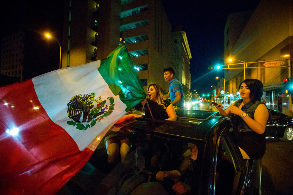 A Mexican flag is waved as people take to the streets after Donald Trump speaks at a rally in Albuquerque, NM during the 2016 U.S. presidential campaign.