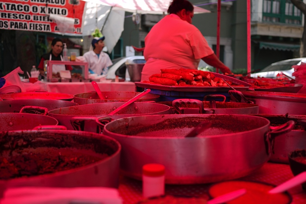 """This is from the farmer's market in the Condessa neighborhood of Mexico City. There were so many bright and vibrant stalls, and I loved the way the bright pink color of the tarp covering this food stand made the entire image glow neon pink. We had delicious food here! """