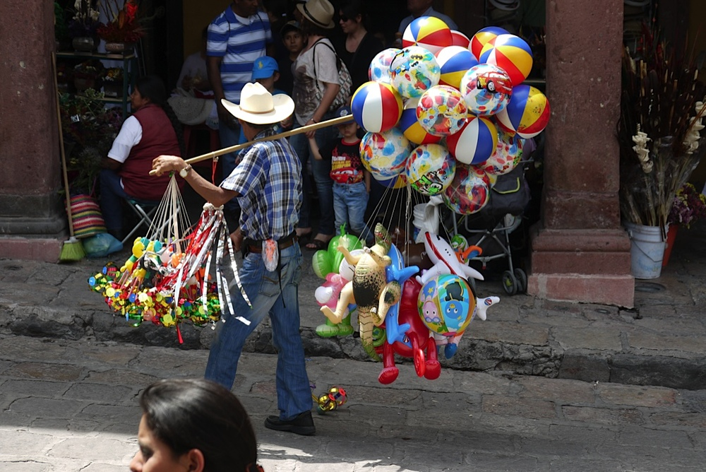 """The main plaza was always packed with people, and I just loved the bright colors of all the things this man was carrying and selling. """