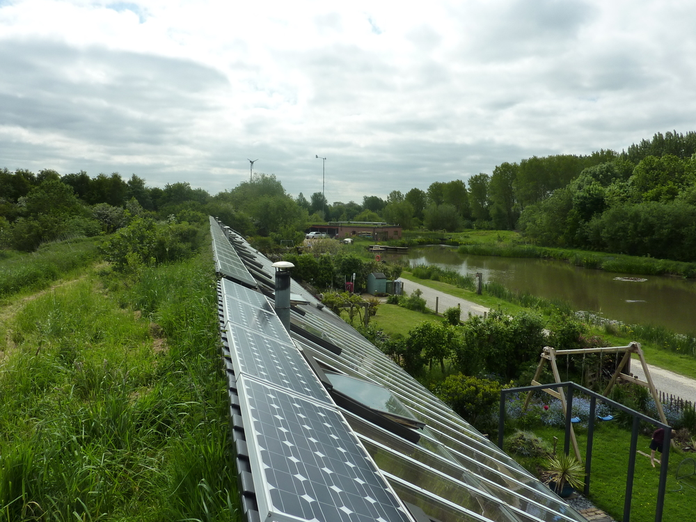 Solar panels run along the building at the junction between the earth covered roof and glazed conservatory. Wind turbines in the distance.