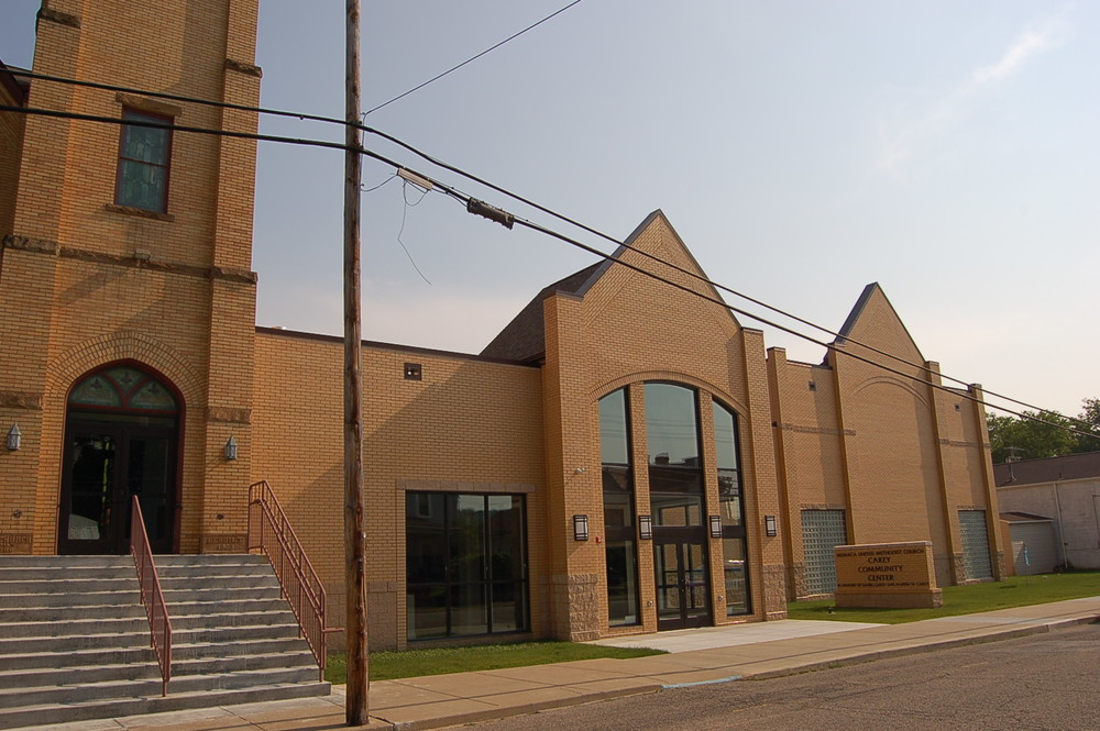 The original 1906 brick church building stands tall on the left while the community center addition blends seamlessly with the existing architecture.