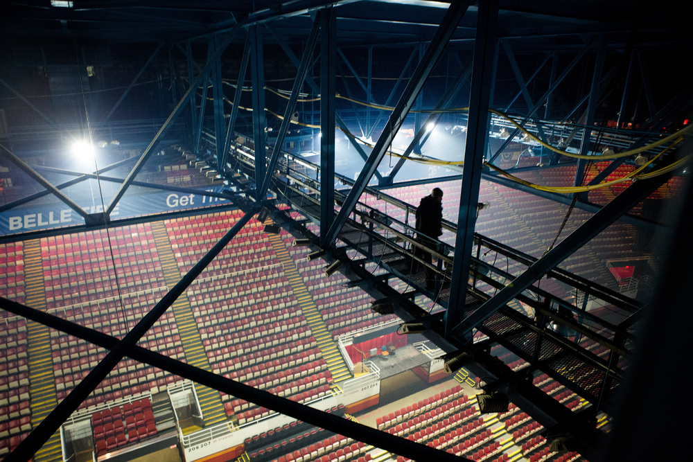 The Glamour of the Catwalk  Climber or not, a Rigger's job is not for the faint of heart. The first ones to work and the last ones to finish, the project begins and ends with them everyday. Here, Cee Phillips walks among the shadows on New Year's Day 2014 @ Joe Louis Arena in Detroit.