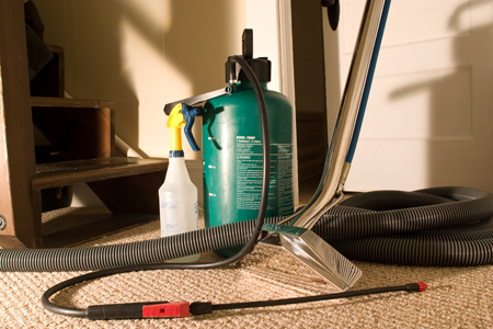 Carpet cleaning equipment including a professional vacuum, clear stain remover spray bottle and a green pump with spray nozzle.