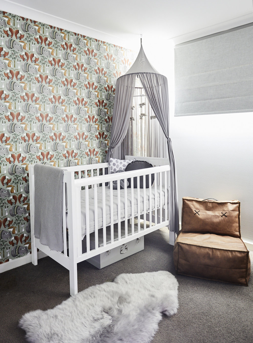 Baby nursery with cot and wall paper