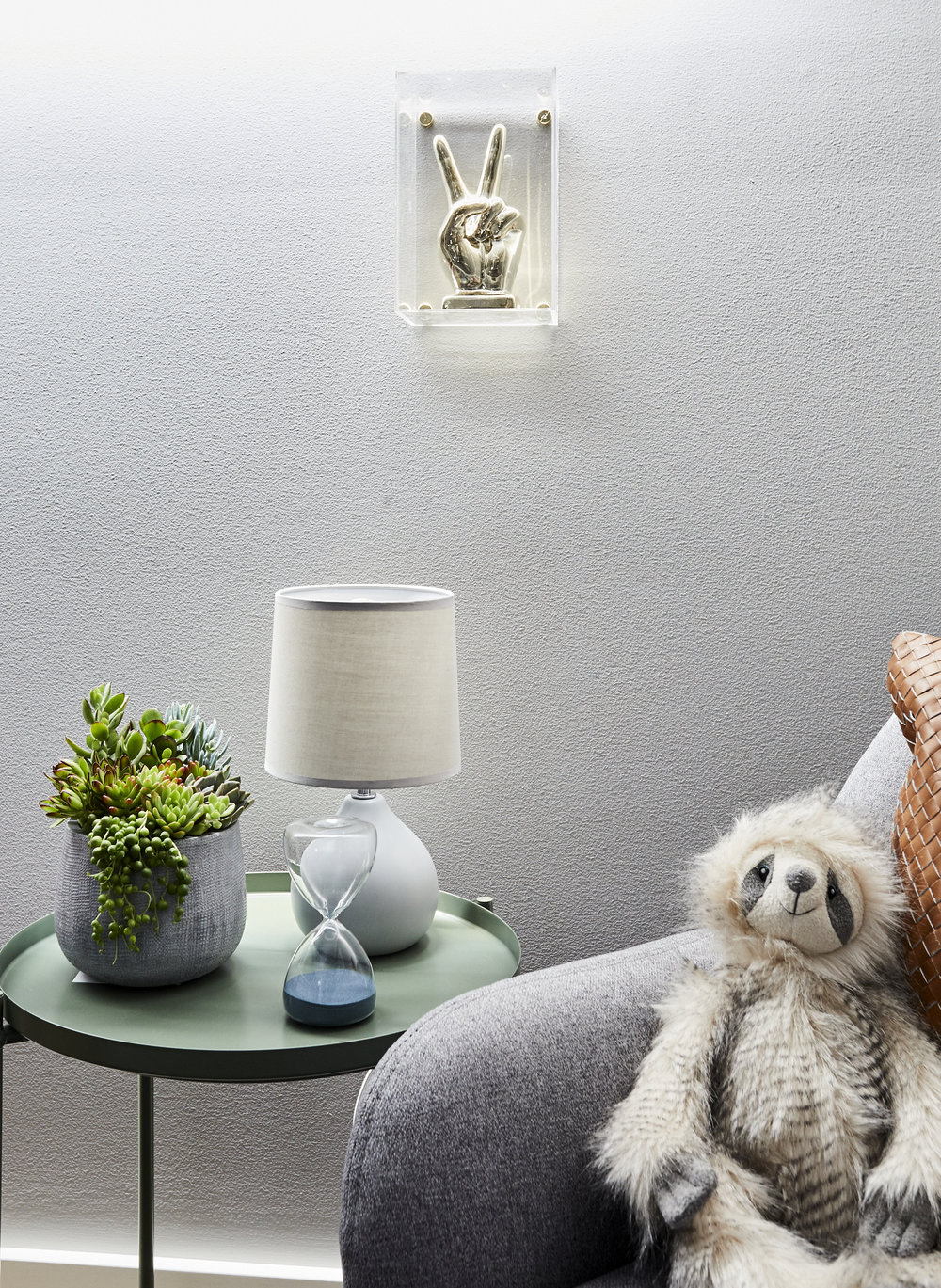 detailed shot of baby nursery with bear, cushion, armchair side table and lamp