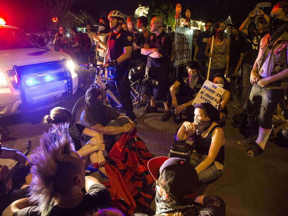 As a police SUV pushed protesters, trying to clear the street, multiple protesters sat down in front of it. It eventually backed out of the street.