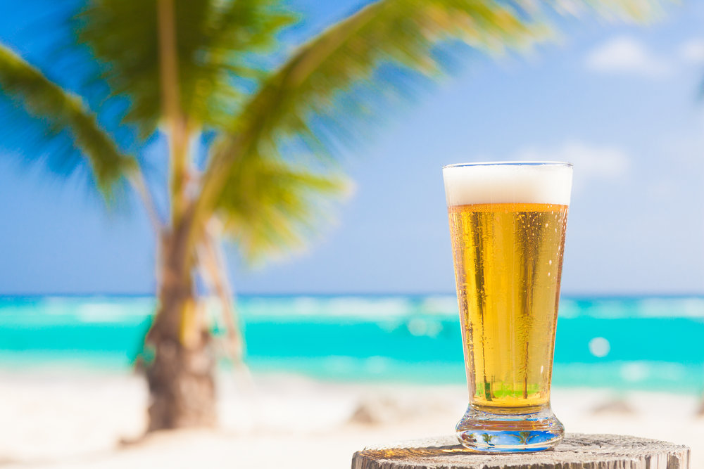shutterstock_374397763.jpg - glass of cool beer on table near beach.jpg
