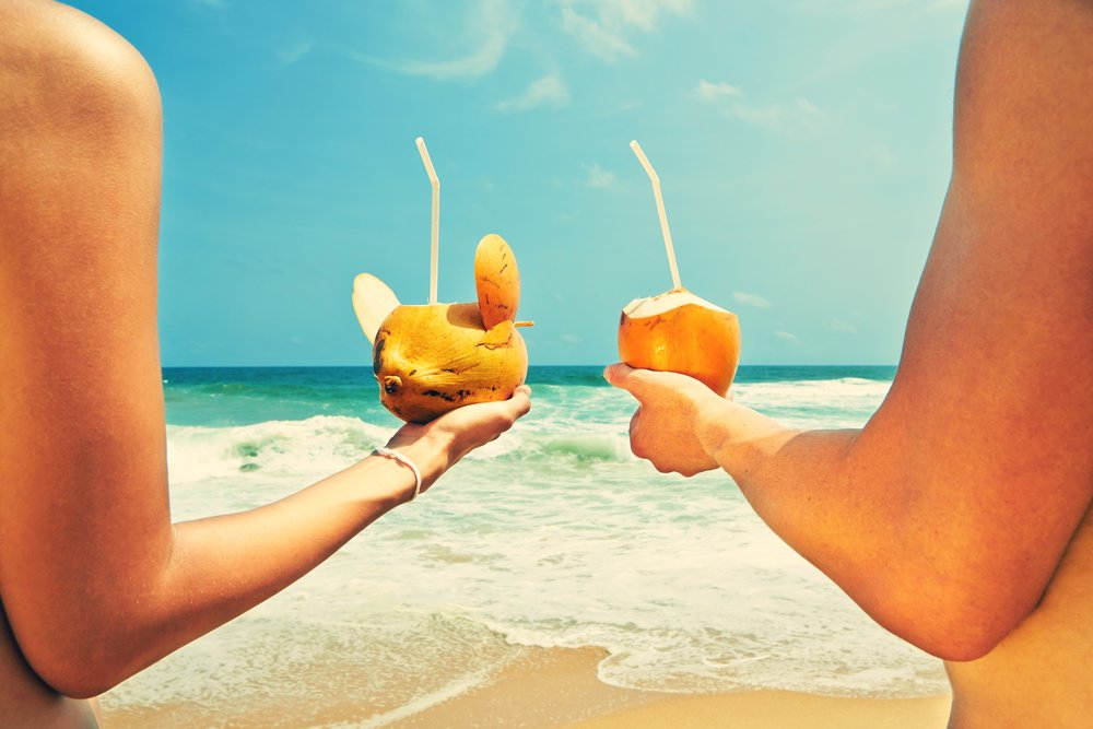 shutterstock_210140635.jpg - Hands of the couple with coconut drinks.jpg