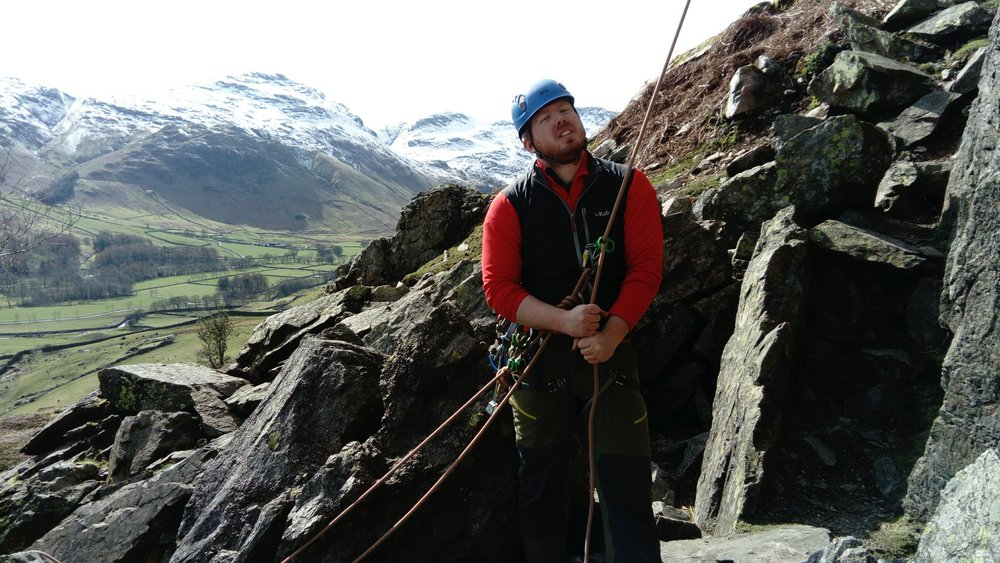 Nathan belaying at the bottom of Stickle Barn crag using a ground anchor