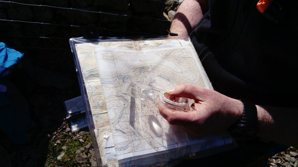 A person holding a map case containing a contour only map – Chris Ensoll Mountain Guide