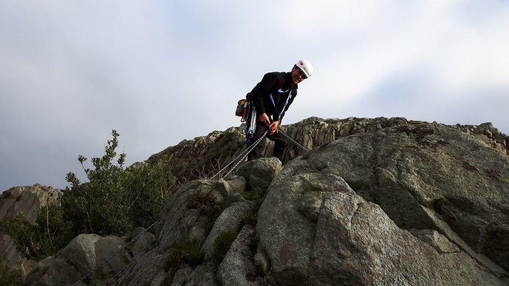 A rock climber setting up an abseil - Chris Ensoll Mountain Guide