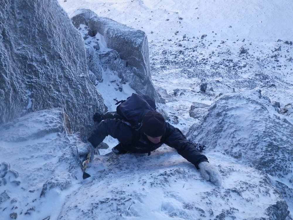 A climber scrambling up a snowy gully - Chris Ensoll Mountain Guide
