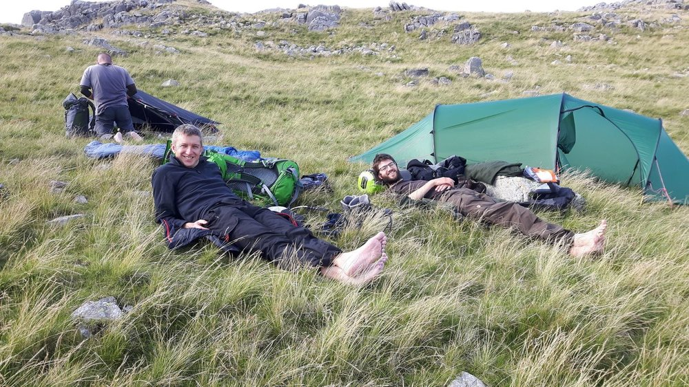 Mountain leader training candidates taking a well-earned rest at their campsite