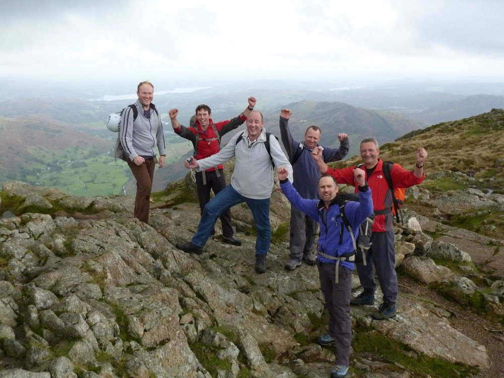 A group of clients celebrating success at the top of a rock climb - Chris Ensoll Mountain Guide