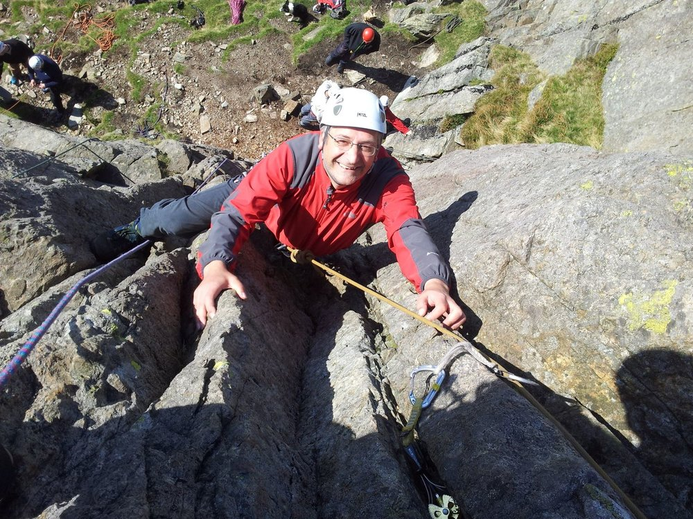 a client climbing a single pitch rock route in the lake district - chris ensoll mountain guide