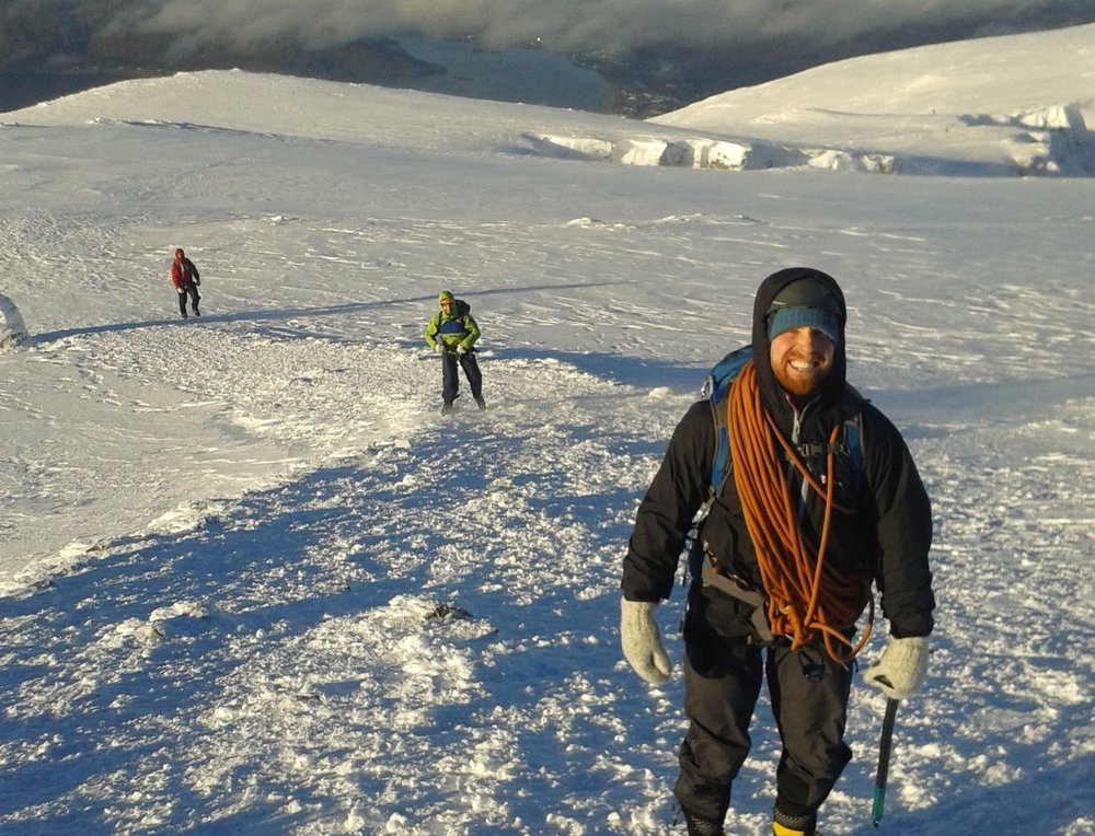 three winter mountaineers walking up a snowy slope