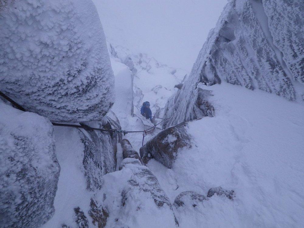 a winter climber climbing a snowy gulley
