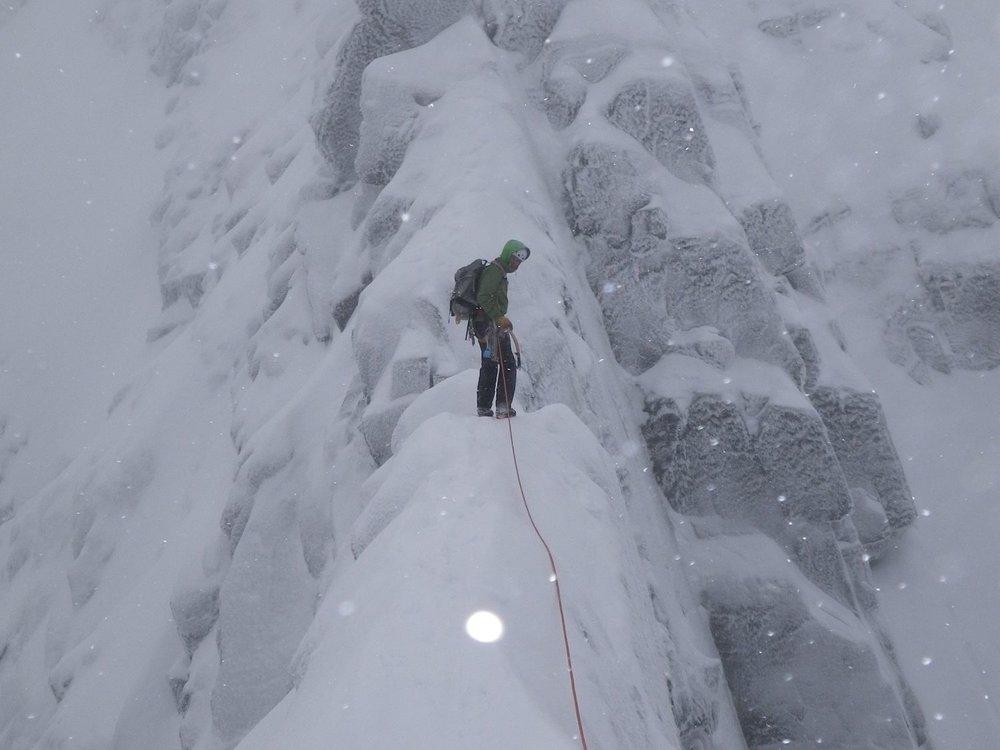 a winter climber lead climbing on a snowy ridge