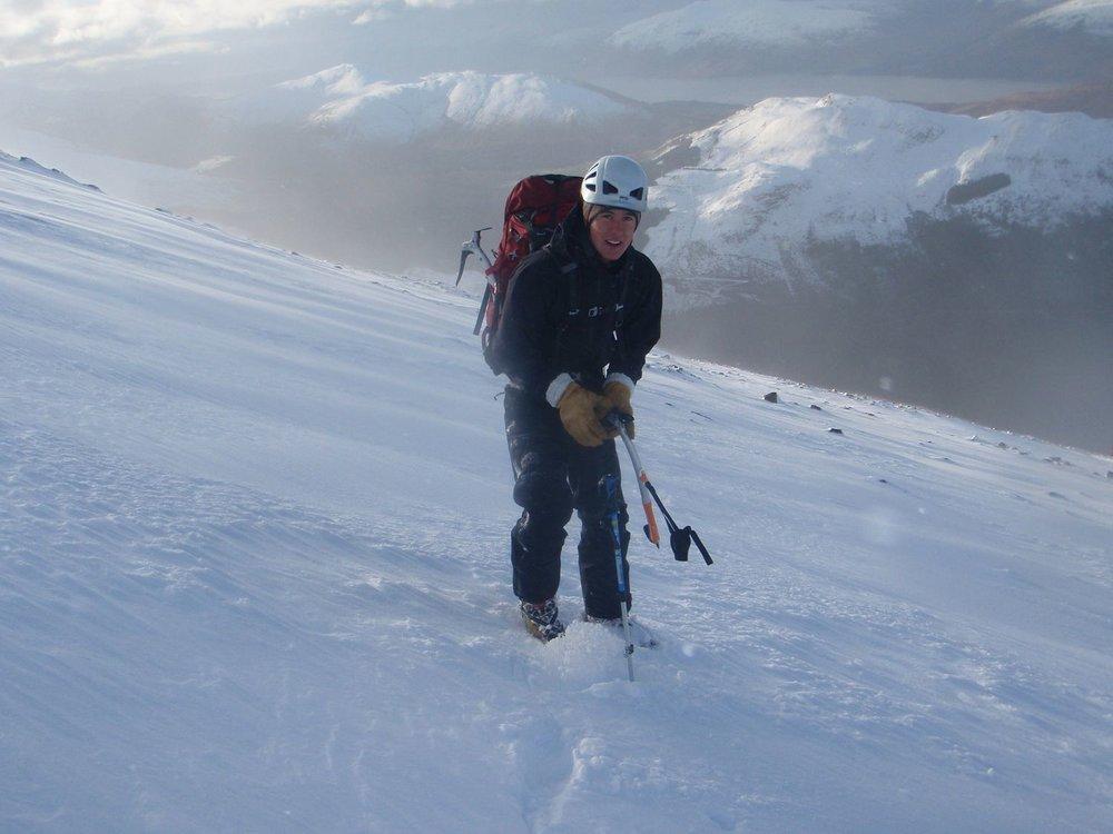 a winter mountaineer makes his way across a snowy mountain
