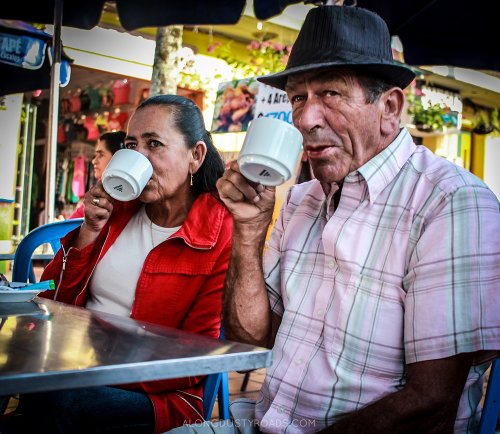 man and lady drinking coffee guatape colombia