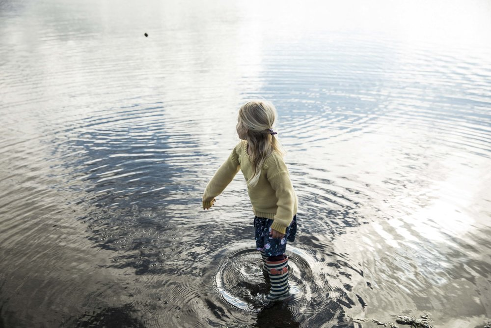 Valtýr Gunnarsson's daughter Freyja throws rocks into the lake near the family's summer house in Laugarvatn