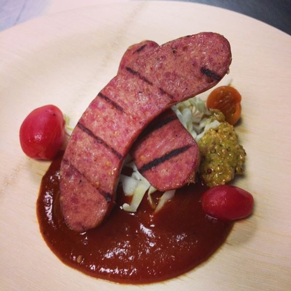 Smoked boar jagerwurst, sauerkraut, rye croutons, heirloom bbq sauce, and grain mustard by Pulaski Heights BBQ.