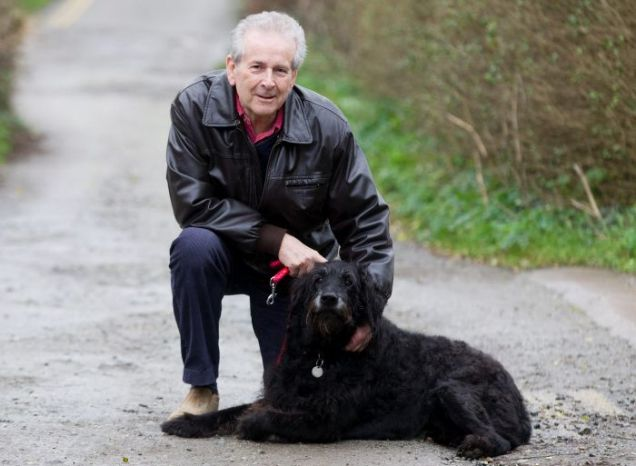 Maurice Holder kneels next to his dog Monty
