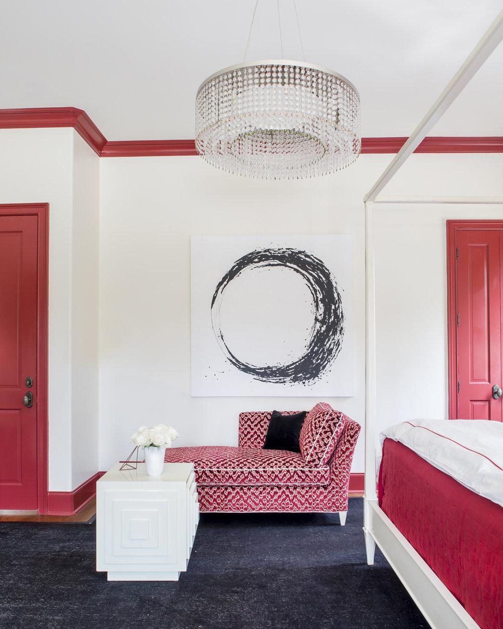 Red, black, and white master bedroom; red doors, crown molding & trim; white canopy bed; abstract modern circular painting; red chaise lounge | Savage Interior Design