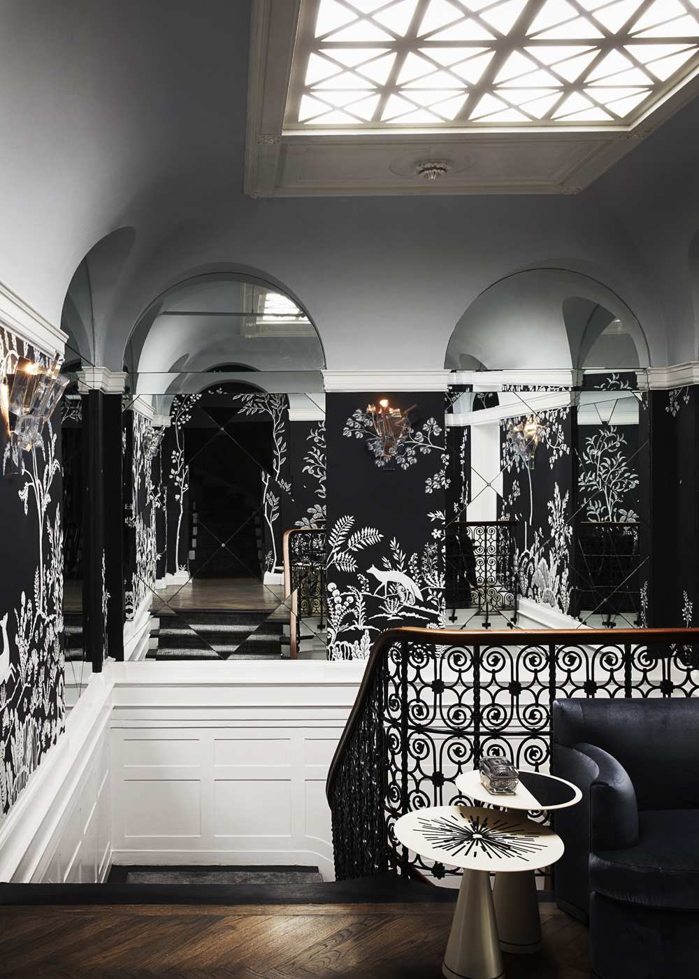 Staircase landing showing custom MJ Atelier wallcovering, scrolling iron stair railing, and mirrored niches | Savage Interior Design