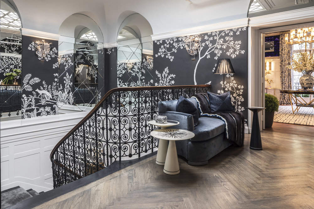 Staircase landing showing custom MJ Atelier wallcovering, scrolling iron stair railing, and herringbone wood floor | Savage Interior Design
