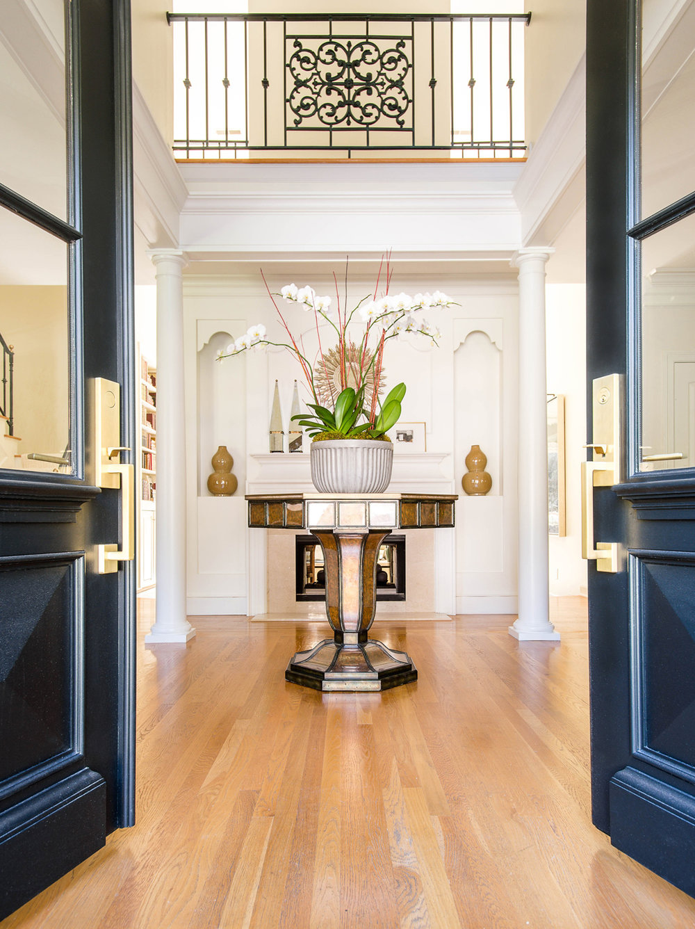Foyer with Art Deco style center table topped with orchids just inside front doors | Savage Interior Design