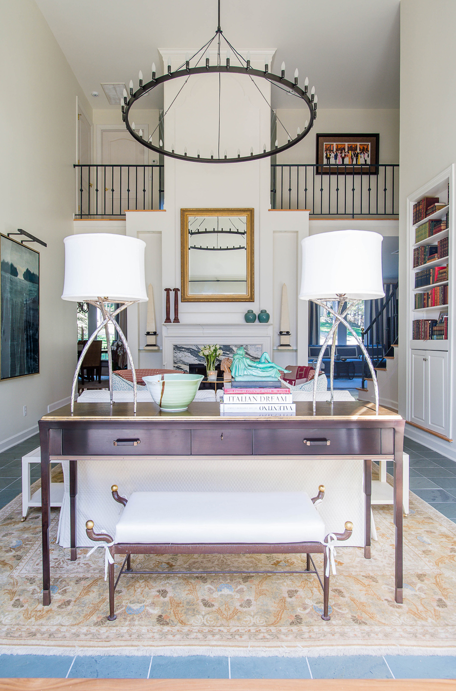 Two-storey living room with console table and bench featured; pair of modern metal lamps on top | Savage Interior Design