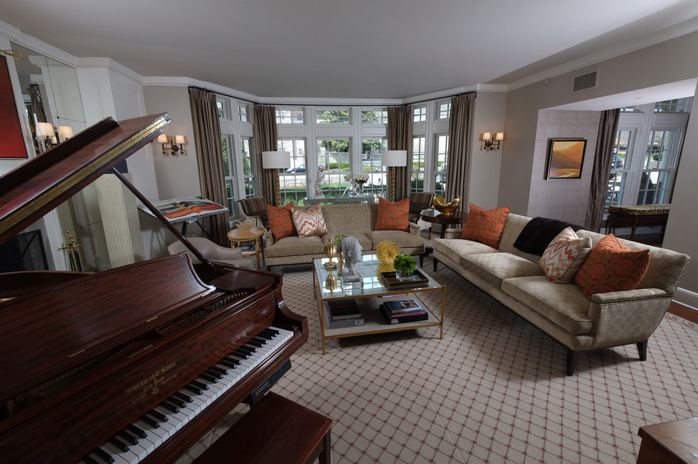 Living room with bay window;  pair of sofas with mirrored coffee table and Steinway piano | Savage Interior Design